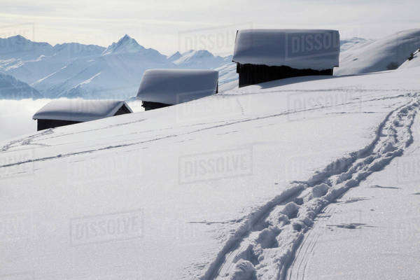 Foot path leading to three snow-capped log cabins Royalty-free stock photo