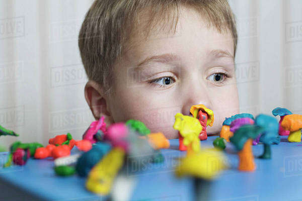 A young boy looking at various shapes made from child's play clay Royalty-free stock photo
