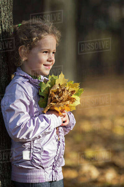 A young cheerful girl holding a bunch of autumn leaves with pride Royalty-free stock photo
