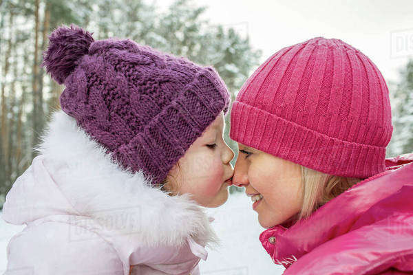 A mother and daughter wearing warm clothing, outdoors, face to face Royalty-free stock photo