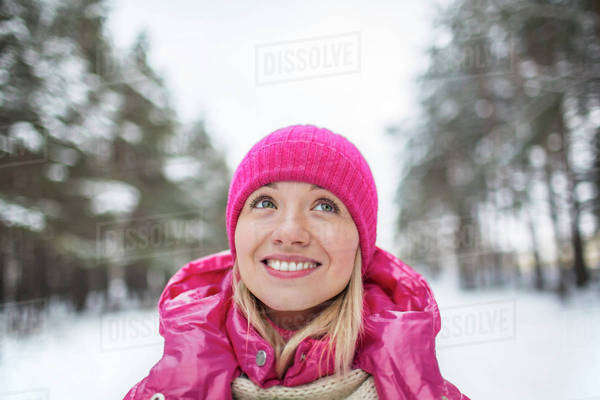 A beautiful woman in a knit cap looking up, outdoors in winter Royalty-free stock photo