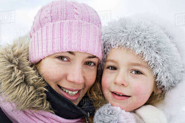 A cheerful mother and daughter in warm clothing outdoors in winter Royalty-free stock photo