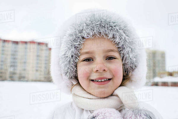 A cheerful young girl wearing warm clothing outdoors in winter Royalty-free stock photo