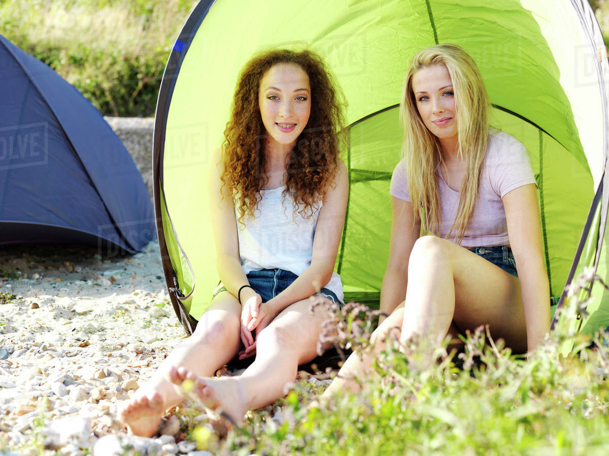 Two teenage girls sitting in a beach tent on a beach