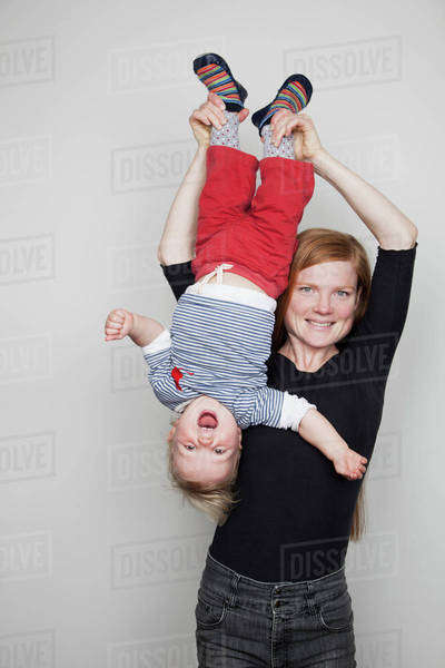 Mother holding baby boy upside down Royalty-free stock photo