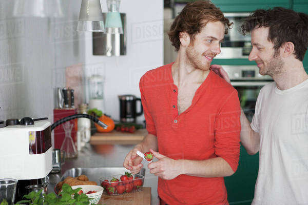 Affectionate gay couple looking at each other in kitchen Royalty-free stock photo