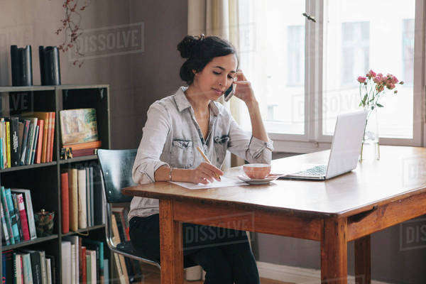 Young woman using mobile phone with laptop on table at home Royalty-free stock photo
