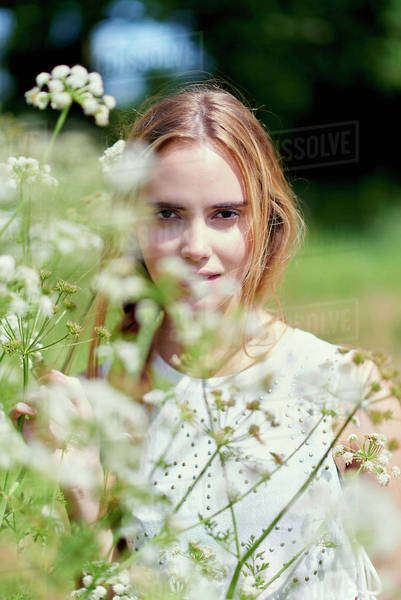 Portrait of young woman standing by flower plants in park Royalty-free stock photo
