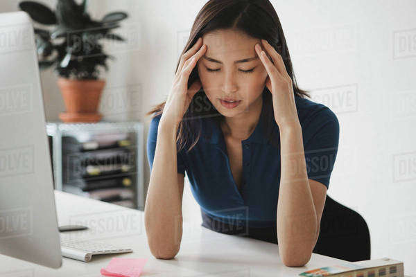 Young businesswoman suffering from headache at desk in office Royalty-free stock photo