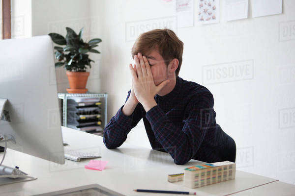 Tired businessman with hands on face at desk Royalty-free stock photo
