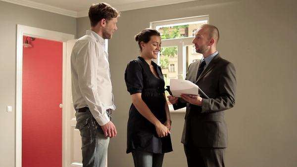 Tilt up, Tilt down, Medium shot of a couple with a real estate agent signing a contract Royalty-free stock video
