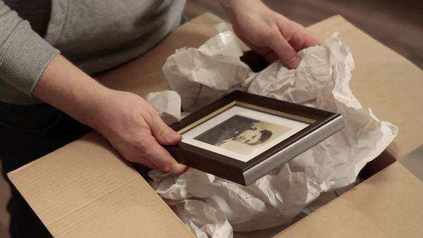 Close-up, High Angle, Tilt down, zoom in of a man packing a photograph of an old-fashioned woman, focus on hands Royalty-free stock video