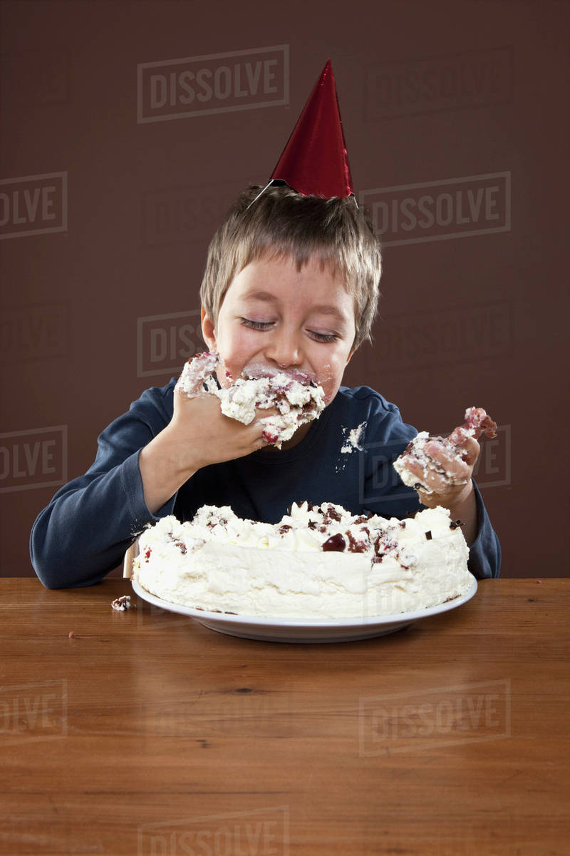 Wondrous A Boy Wearing A Party Hat Eating Birthday Cake With His Hands Funny Birthday Cards Online Inifofree Goldxyz