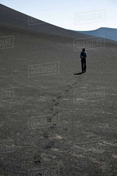Rear view of a woman walking over Lonquimay Volcano, Patagonia, Chile Royalty-free stock photo