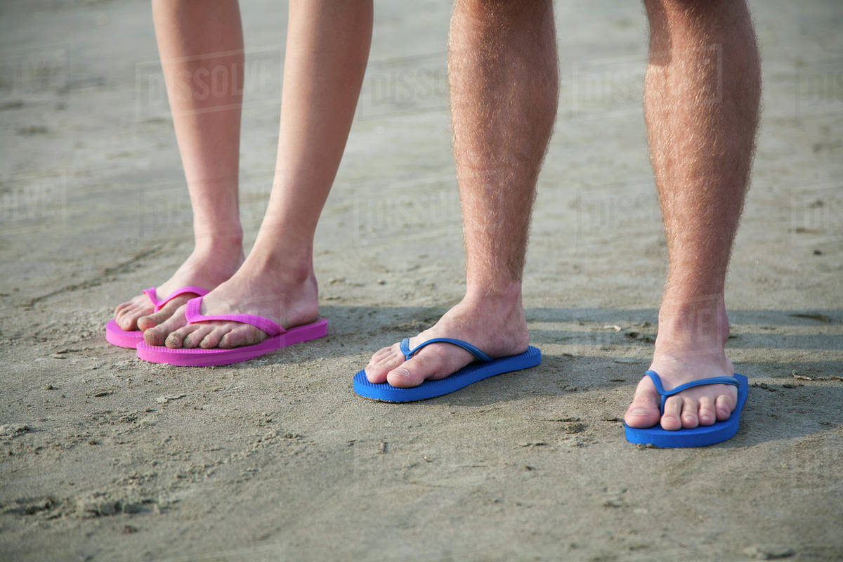 2182ac8c8d58 A young couple wearing flip-flops at the beach