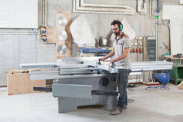 Full length of carpenter using a sliding table saw in workshop Royalty-free stock photo