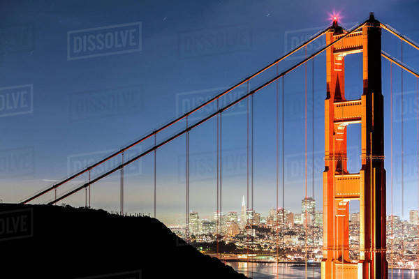 Golden Gate Bridge with illuminated cityscape in background Royalty-free stock photo