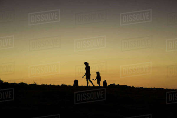 Silhouette woman and boy walking on field against clear sky during sunset Royalty-free stock photo