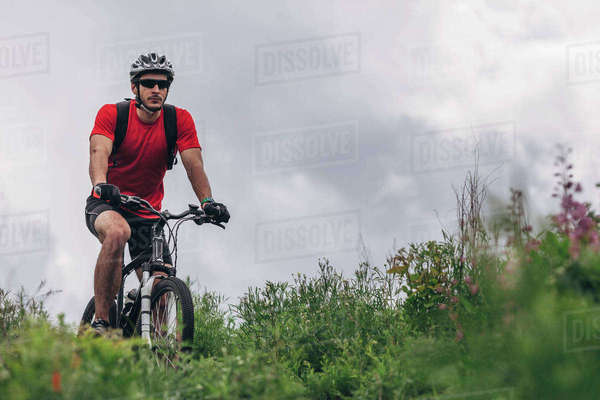 Determined man riding mountain bike against cloudy sky Royalty-free stock photo