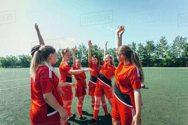 Excited soccer players with hands raised standing on field Royalty-free stock photo