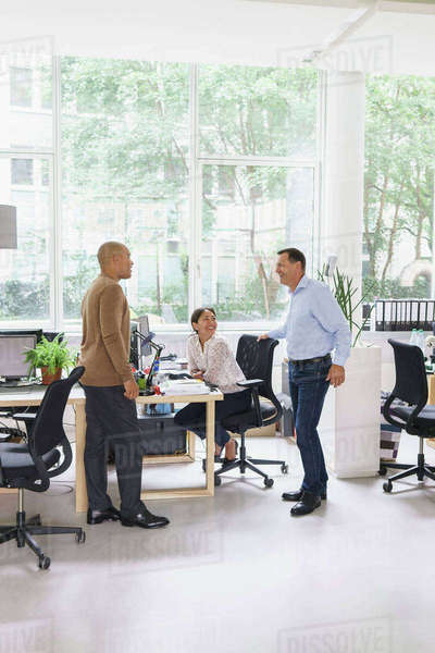 Happy businessmen communicating with female colleague at creative office Royalty-free stock photo