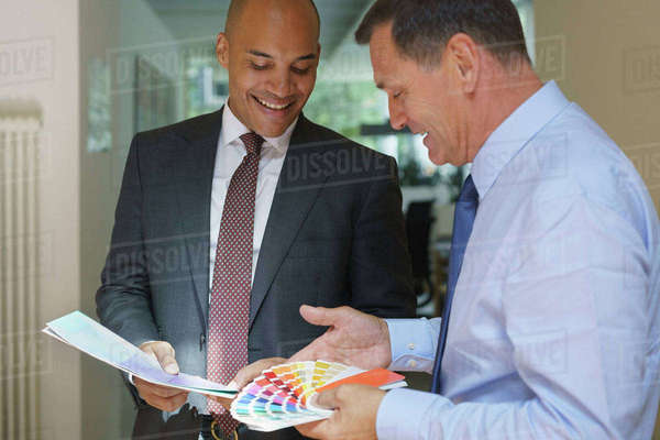 Smiling confident businessmen discussing over color swatches at creative office Royalty-free stock photo