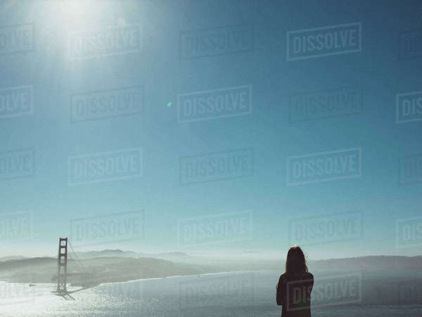 Rear view of woman looking at broken bridge over sea against clear blue sky Royalty-free stock photo