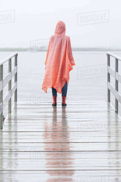 Rear view of woman wearing raincoat standing on jetty during rainy season Royalty-free stock photo