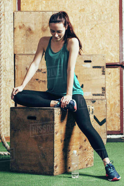 Full length of female athlete sitting on wooden box at gym Royalty-free stock photo