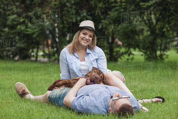A man napping with his dog lying on him while his girlfriend relaxes by him Royalty-free stock photo