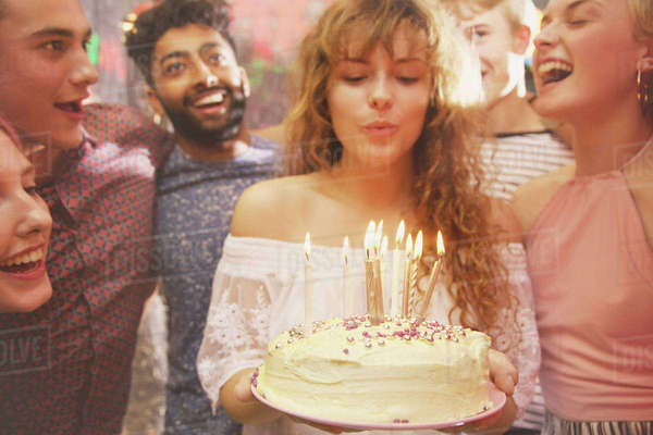 Woman blowing candles while celebrating birthday with friends Royalty-free stock photo
