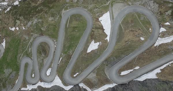 Aerial view of cars moving on winding road amidst mountains during winter, Tremola Road, Switzerland Royalty-free stock video