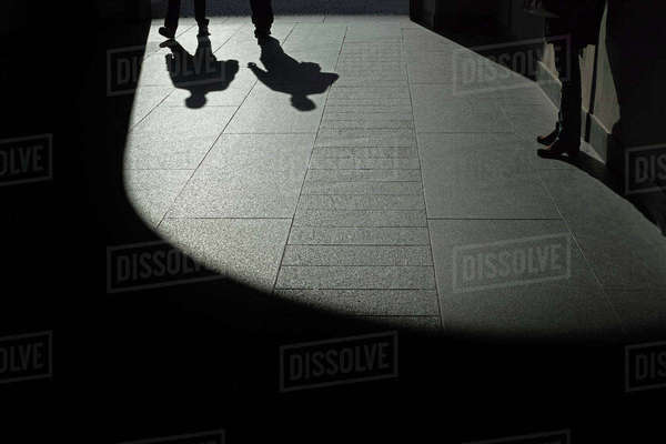 Low section of people in shadow on sidewalk Royalty-free stock photo