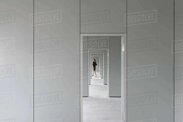 View through corridor of businesswoman walking in office Royalty-free stock photo