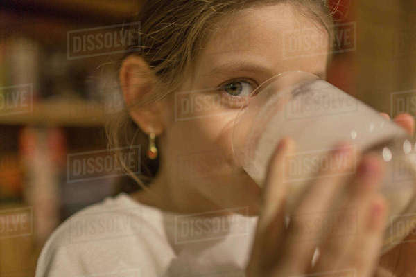 Close-up portrait of cute girl drinking milk at home Royalty-free stock photo