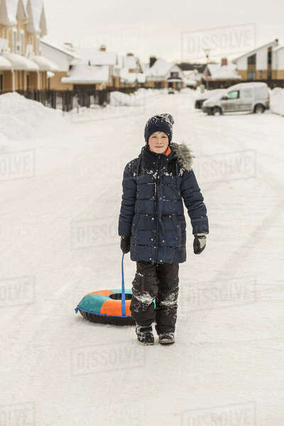 Full length portrait of boy pulling inflatable ring in snow Royalty-free stock photo