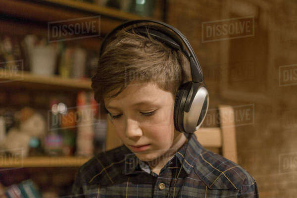 Boy listening music through headphones at home Royalty-free stock photo
