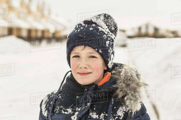 Portrait of confident boy in winter wear covered with snow Royalty-free stock photo