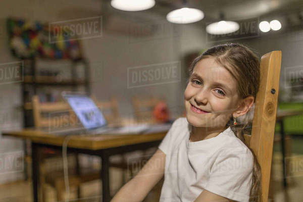 Portrait of smiling girl sitting on wooden chair at home Royalty-free stock photo