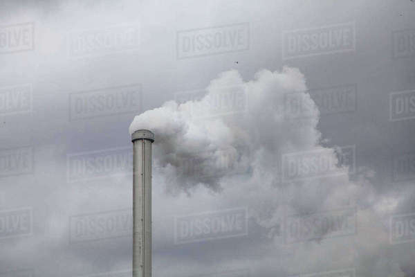 Low angle view of smoke emitting from chimney against cloudy sky Royalty-free stock photo