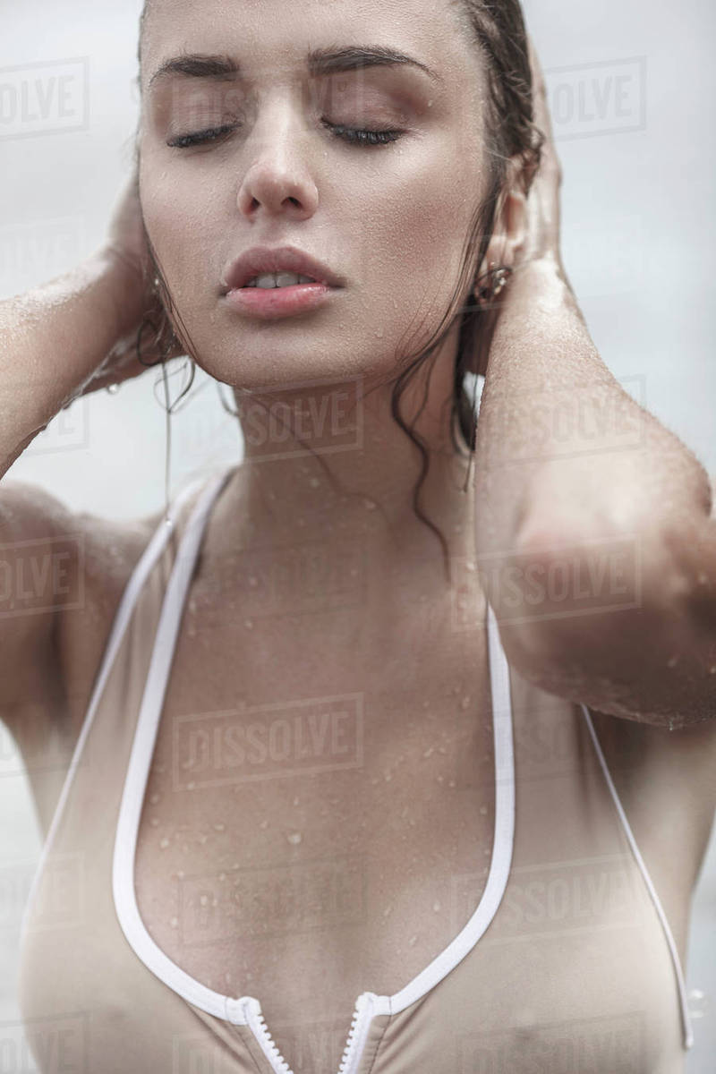 Close Up Of Sensuous Young Woman With Closed Eyes Touching Wet Hair