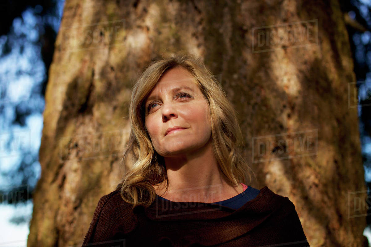 Portrait serene woman standing at sunny tree trunk Royalty-free stock photo