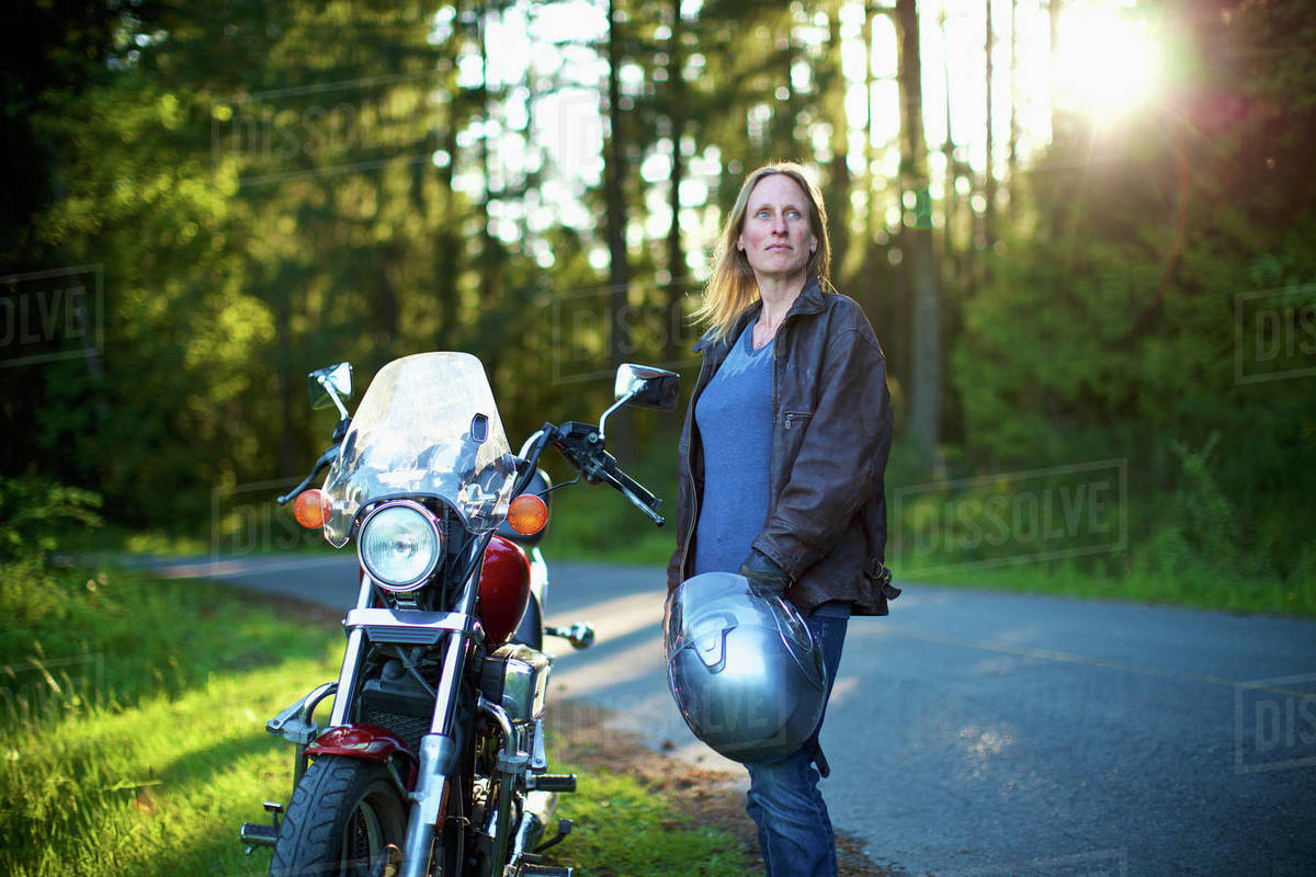 Confident woman standing at motorcycle at roadside in woods Royalty-free stock photo
