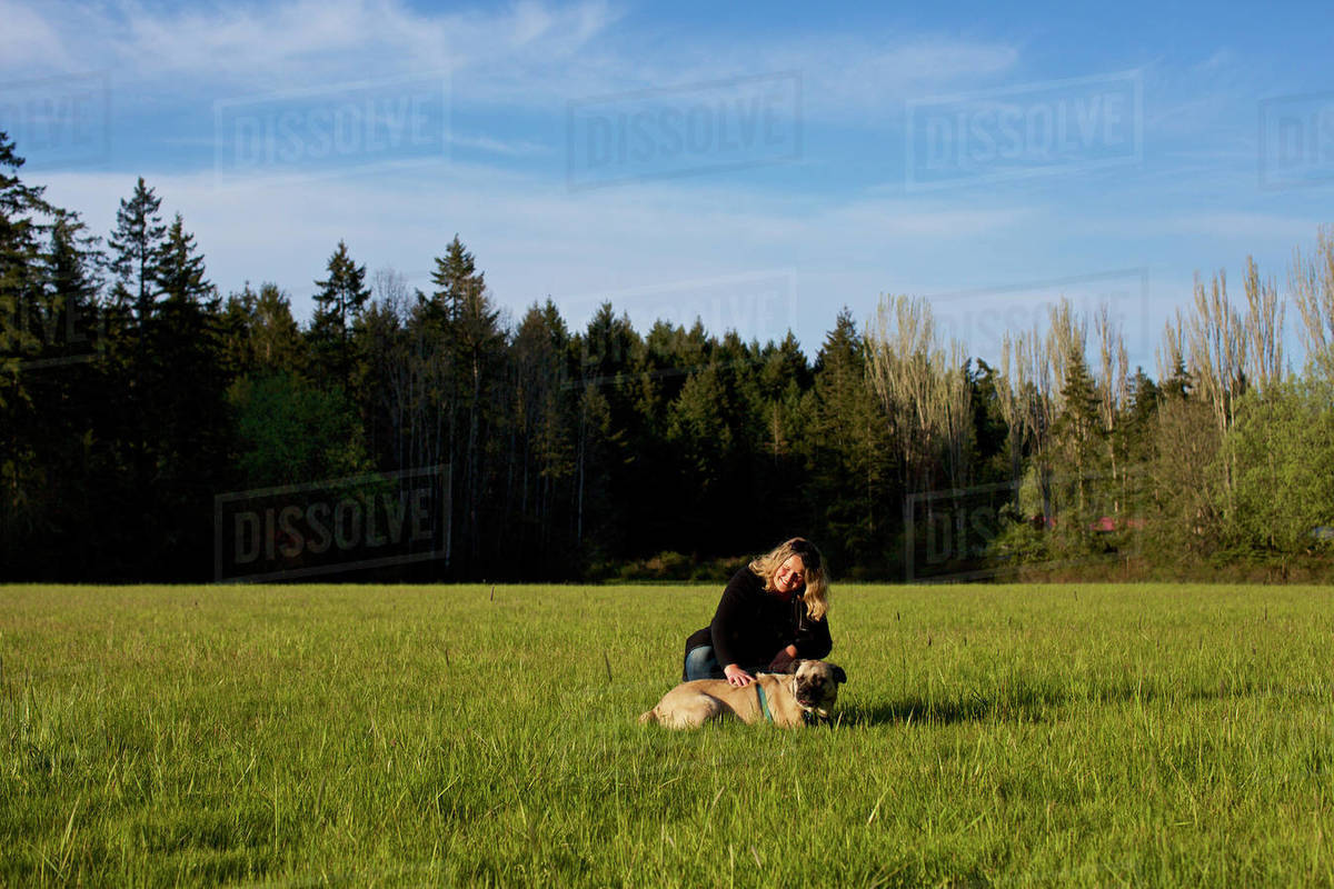 Woman with dog in sunny, rural field Royalty-free stock photo