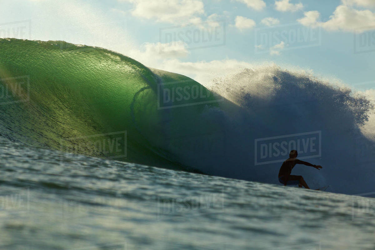 Silhouetted male surfer riding ocean wave Royalty-free stock photo