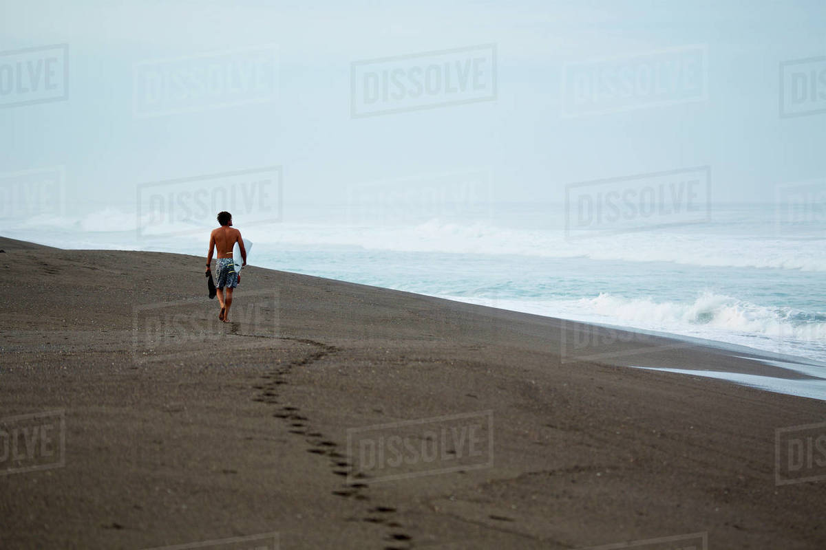 Male surfer walking with surfboard on wet sand beach Royalty-free stock photo
