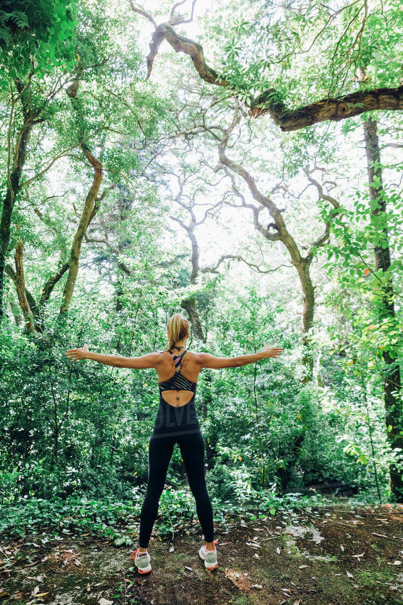Fit female personal trainer exercising, stretching arms in forest Royalty-free stock photo
