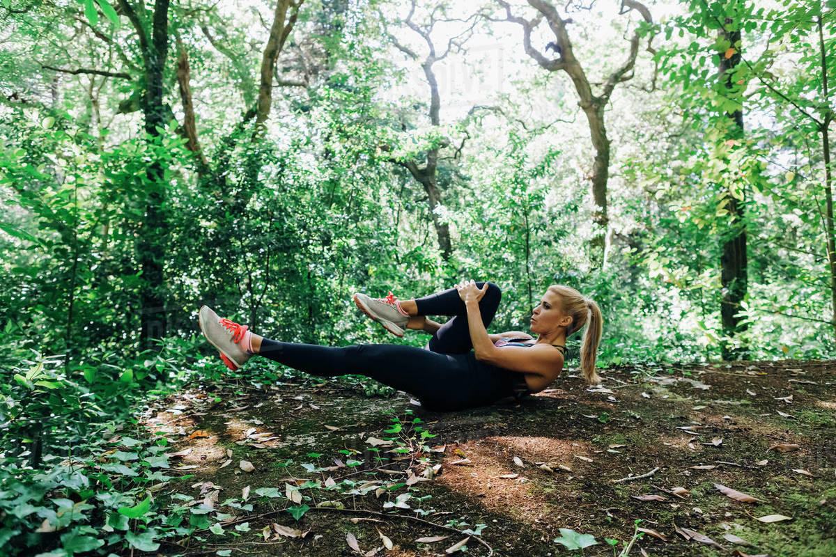 Fit female personal trainer exercising, stretching legs in forest Royalty-free stock photo