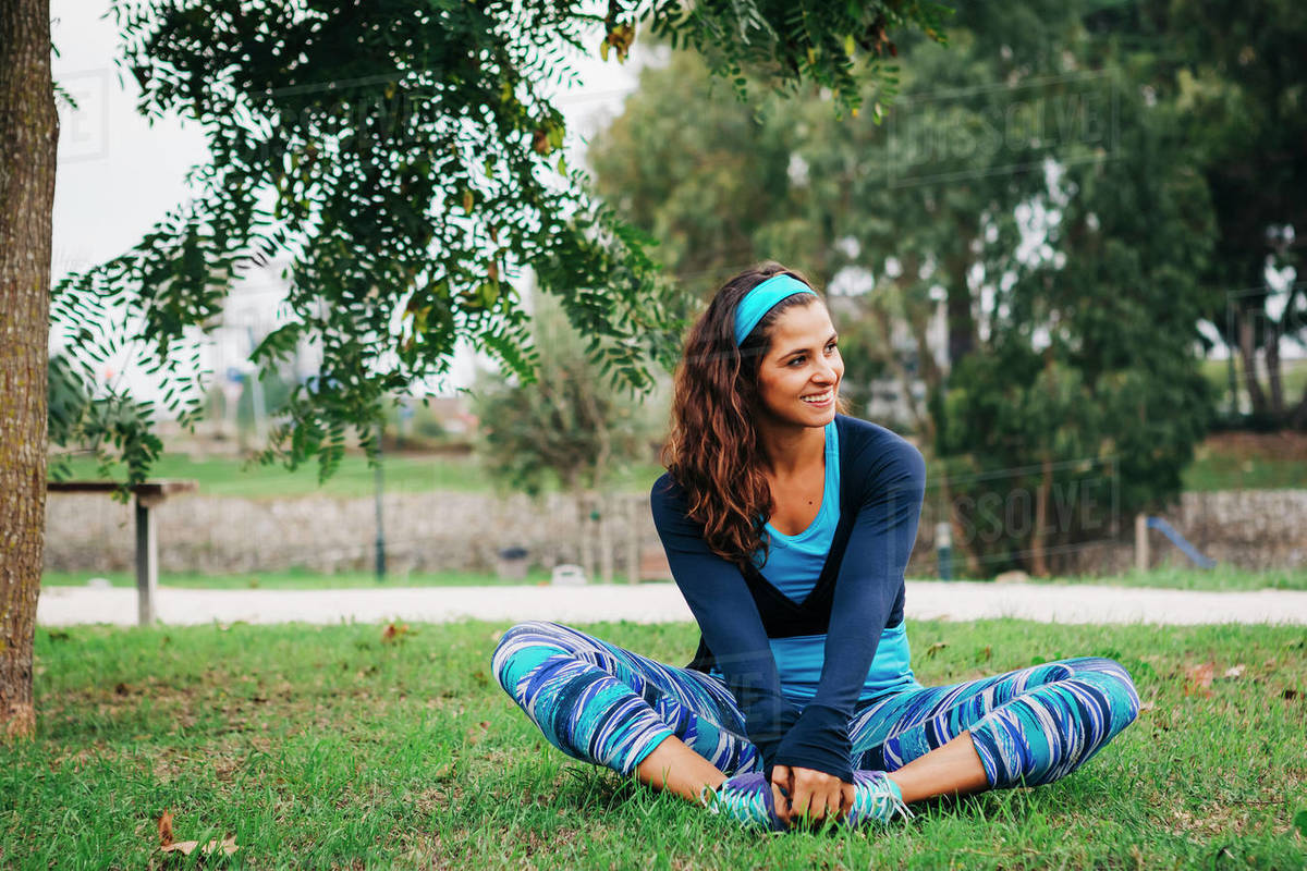 Smiling, fit female trainer exercising, stretching in park Royalty-free stock photo