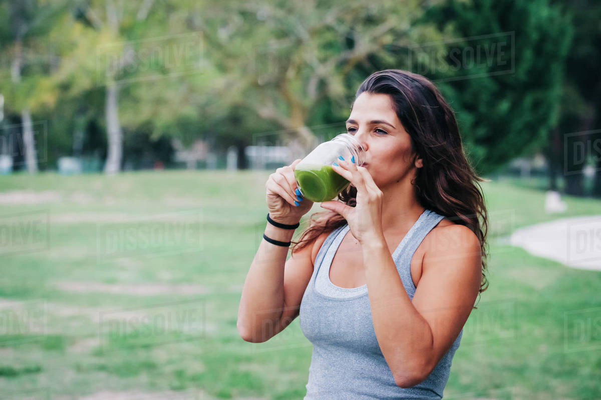 Fit female personal trainer drinking green smoothie in park Royalty-free stock photo